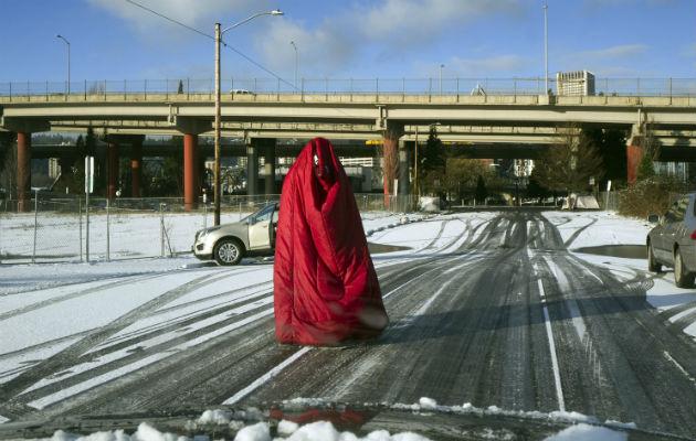 Un hombre camina por la calle cubierto con una bolsa de dormir ante el intenso frío en Portland, Oregon. Foto: AP.