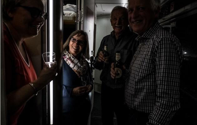 Pasajeros conviven en el pasillo del vagón dormitorio disfrutando bebidas en el Nightjet. Foto / Maxim Babenko para The New York Times.