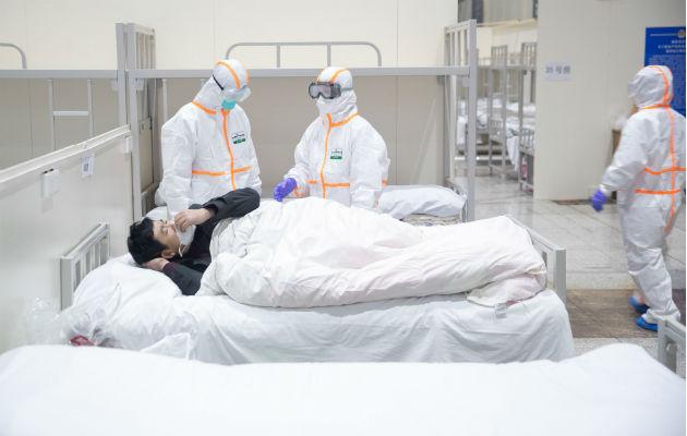Socorristas con trajes de bioseguridad cuando retiraban un cadáver de una calle de Wuhan, China. Fotos: Archivo/Ilustrativa.