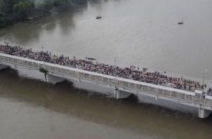 Al menos un millar de migrantes permanecen aparcados en el puente fronterizo en espera de ser atendidos. EFE