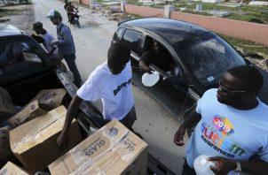 Voluntarios entregan agua y alimentos a los sobrevivientes del huracán Dorian en Bahamas. AP