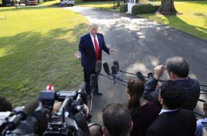 El presidente Donald Trump, atiende a un grupo de periodistas que lo cuestionan sobre Irán. FOTO/AP