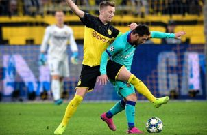 Marco Reus disputa (izq.) el balón ante Messi. AP