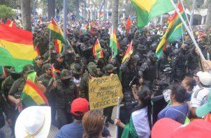 Un grupo de policías ondea la bandera tricolor de Bolivia mientras se repliega a una comisaría. FOTO/EFE