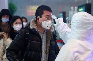 Personal médico chequea la temperatura de una persona en Nanjing, China como medidas de prevención contra el coronavirus. Foto EFE