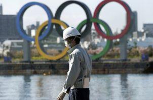 Un hombre trabaja con los anillos olímpicos fe fondo en el distrito de Odaiba en Tokio. Foto:AP
