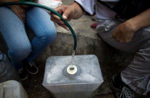 Un grupo de personas hacen una inmensa fila para lograr abastecerse de agua de un camión cisterna. FOTO/AP