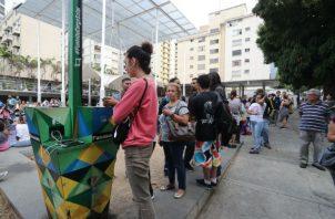 Personas hacen fila para recargar la batería de sus teléfonos móviles en un punto público durante el apagón eléctrico en Caracas. Foto: EFE.
