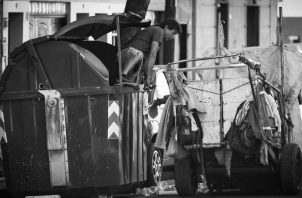 Un hombre busca en un viejo contenedor de basura en Buenos Aires. Autoridades intentan colocarle cerrojos para evitar que ensucien las calles con los restos de basura. Foto: EFE