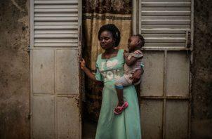 Veronique Fara, pareja de Fiacre Gbédji, un guía en Benín que fue asesinado, con la hija de 2 años de ambos. Foto/ Finbarr O'Reilly para The New York Times.