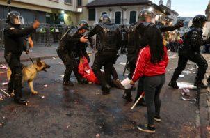 Policías se enfrentan a manifestantes durante una protesta de apoyo a favor del australiano Julian Assange, en Quito. Foto: EFE.