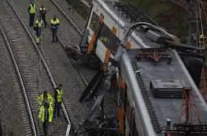 Bomberos y trabajadores de emergencia están parados junto a los vagones descarrilados del tren cerca de Barcelona. EFE