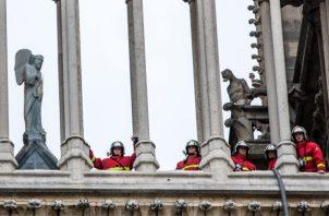 Bomberos permanecen entre las columnas de la catedral de Notre Dame después del incendio sufrido este lunes, en París. FOTO/EFE