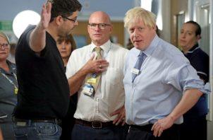 Omar Salem, cuya hija está siendo tratada, en el pabellón de niños Acorn, hace gestos mientras habla con el primer ministro británico, Boris Johnson, durante su visita al Hospital Universitario Whipps Cross en Leytonstone, este de Londres. FOTO/AP