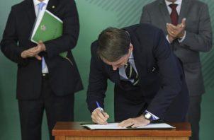 Jair Bolsonaro, cumple con una de sus promesas de campaña electoral y firma un decreto sobre armas.. FOTO/AP