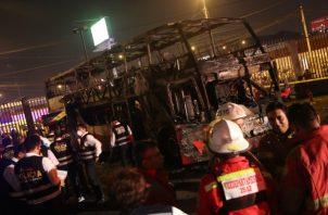 Equipos de bomberos y de la Policía Nacional inspeccionan este domingo los restos calcinados del autobús de la empresa Sajy Bus que se incendió en la terminal de autobuses de Fiori, ubicada en el distrito de San Martín de Porres, en Lima. FOTO/EFE
