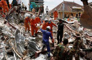 364/5000 Un equipo de rescate camboyano lleva el cuerpo de un trabajador al sitio de un edificio derrumbado en un sitio de construcción en la provincia de Preah Sihanouk. FOTO/AP