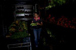 Una mujer compra en una tienda de comestibles a oscuras en Caracas, FOTO/AP