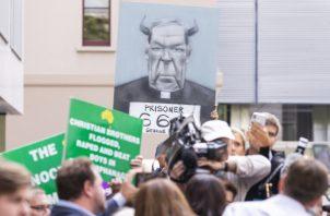 Un grupo de personas que protestan reaciconan al saber la sentencia del cardenal George Pell. FOTO/EFE
