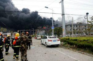 Bomberos en las afueras de la fábrica siniestrada. Foto: AP.