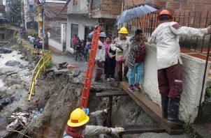 Un grupo de personas cruzan por una de las zonas afectadas en el barrio El Pesebre, luego que la quebrada La Iguaná se desbordara la noche anterior por las fuerte lluvias, en Medellín. FOTO/EFE