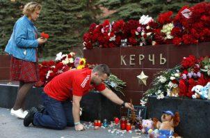 La gente trae flores y velas para honrar a las víctimas del ataque del miércoles a una escuela vocacional en Kerch, Crimea. AP