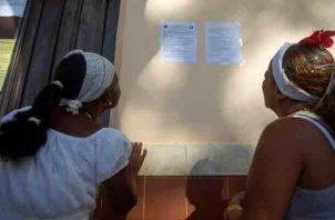 Unas mujeres se acercan a leer las predicciones de los santeros. EFE