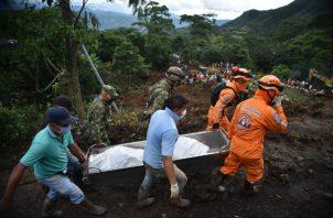 Socorristas trasladan cuerpos tras el deslizamiento de tierra, en la vereda Portachuelo, en el municipio de Rosas, Cauca. Foto: EFE.