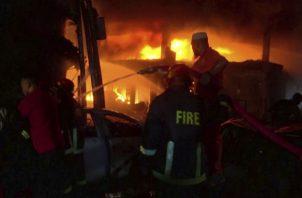 Bomberos combatiendo el incendio. Foto: AP.