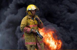 Un bombero solicita ayuda tras quedarse sin agua entre los escombros que dejó una fuerte explosión en una fabrica de plásticos. FOTO/EFE
