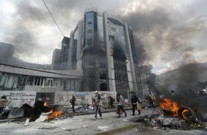Manifestantes tras una barricada de piedras que bloquea una calle este sábado, en Quito. Foto: EFE.