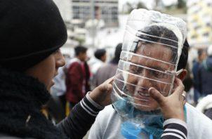 Manifestantes usan máscaras antigas elaboradas por el ecuatoriano Cesar Viteri este jueves en Quito. Foto: EFE.