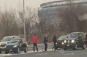 Una camioneta de la empresa de seguridad Brink's se hizo hacia un lado de la autopista con las luces intermitentes encendidas mientras los billetes volaban por la carretera.