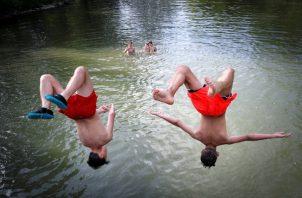 Varios jóvenes combaten el calor este miércoles en el río Arga a su paso por Pamplona, donde las altas temperaturas extremas continuarán como en la mayor parte de España, hasta el próximo lunes. FOTO/EFE