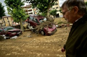 Los residentes caminan en la calle junto a los autos dañados después de las fuertes lluvias en Tafalla, en el norte de España. FOTO/AP