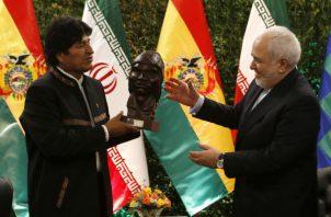 Evo Morales (izq.) entrega una estatuilla al canciller iraní Mohammad Javad Zarif, en su reunión en Santa Cruz. Foto: AP.