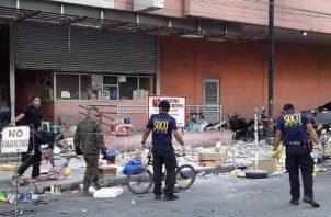 Miembros de la Operación Crimen de la Policía Nacional de Filipinas (SOP) reúnen evidencias en el lugar de una explosión en la víspera de Año Nuevo en las afueras de un centro comercial en la ciudad de Cotabato, al sur de Filipinas. FOTO/AP