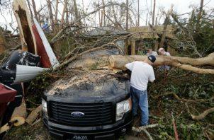 La gente corta un árbol que cae en un vehículo después del huracán Michael en la ciudad de Panamá, Florida. AP