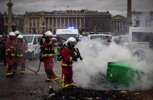 Bomberos apagan un fuego iniciado por conductores de ambulancias que participan en una protesta ante la Asamblea Nacional, en París,