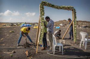 Los trabajadores construyen instalaciones florales en la escena en la que el Boeing 737 Max 8 de Ethiopian Airlines se estrelló poco después del despegue el domingo matando a los 157 a bordo, cerca de Bishoftu, o Debre Zeit, al sur de Addis Abeba, en Etiopía. FOTO/AP