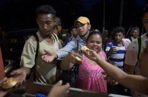Los migrantes hondureños reciben pan gratis de los residentes de Esquipulas, Guatemala. FOTO/AP