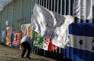 Un migrante hondureño frente a la valla entre Tijuana (México) y EE.UU. Foto: AP.
