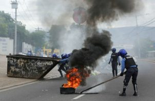 Un policía quita neumáticos en llamas tras enfrentamientos con manifestantes en Tegucigalpa. Foto: EFE.