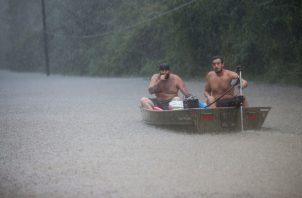 Un par de hombres se suben a un bote para flotar y rescatar a una familia atrapada por las inundaciones cuando la lluvia de la depresión tropical Imelda. FOTO/AP