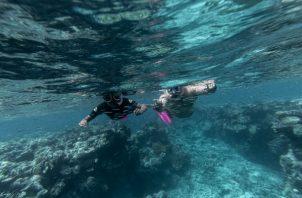 Murrumu de Walubara haciendo snórquel con su hijo en la Gran Barrera de Coral, que, dice, es territorio indígena. Foto/ Brook Mitchell para The New York Times.