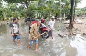 Vecinos recogen escombros en una de las áreas devastadas por el tsunami en Sunda Strait en Carita, Banten, Indonesia. EFE