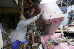 Los residentes limpian los escombros de las casas luego del tsunami en Carita, Indonesia. AP