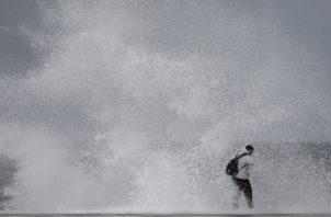 Un ciudadano desafía el fuerte oleaje en la playa de Barceloneta, durante el temporal marítimo que afecta a toda la costa catalana lo que ha obligado a activar la alerta naranja. Foto: EFE