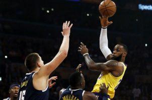 LeBron James (der.) atrapa el balón ante la marca de Nikola Joki de los Nuggets. Foto:AP