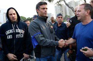 El líder de la oposición, Leopoldo López, en el centro, es recibido por un partidario que se encuentra fuera de la base aérea de La Carlota en Caracas, Venezuela. FOTO/AP